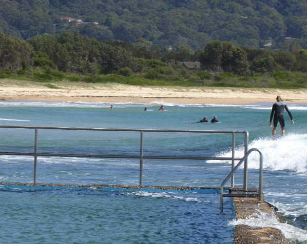 Surfer gliding past rock pool at Bellambi